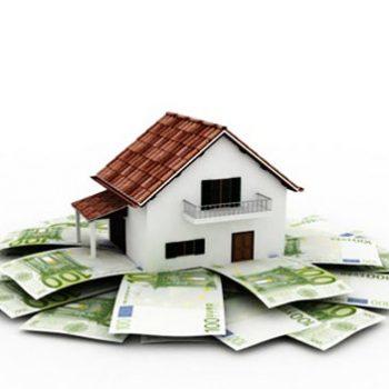 Une maison est bâtie sur des fondations en billets de banque, représentant l'économie d'argent que prodigue les investissements dans l'immobilier grâce au taux immobilier actuel qui est au plus bas.
