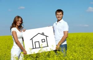 Un couple tient un cadre de tableau sur lequel est dessiné grossièrement une maison, avec des traits noirs. Cela peut représenter à la fois le crédit hypothécaire qu'ils comptent faire ou le crédit immobilier auquel ils voudraient souscrire.