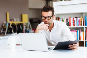 Un homme regarde pensivement son ordinateur portable, cherchant à faire une demande de credit en ligne pour ses projets.